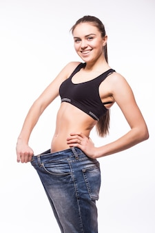 젊은 여자는 오래된 청바지를 입고 그녀의 체중 감소를 보여줍니다