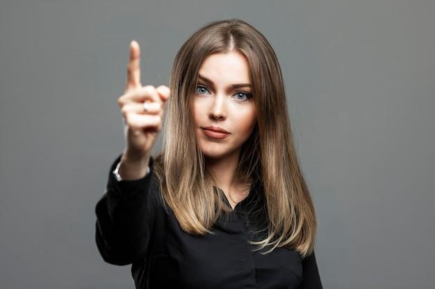 젊은 여자는 검지 손가락을 보여줍니다. 검은 셔츠에 아름 다운 심각한 금발입니다. 회색 배경입니다.