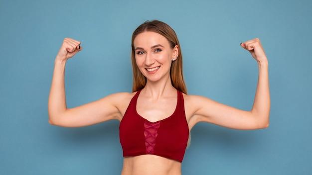 若い女性は青い背景の上腕二頭筋を披露します