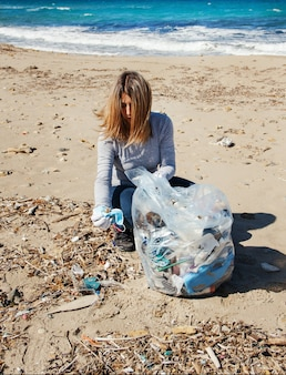 Молодая женщина показывает хирургическую маску во время уборки пляжной зоны