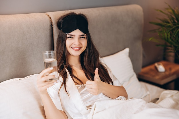 Young woman shows that drinking water is in the bed. model with brown hair with a glass of water in the bed in the bedroom. drink a glass of water in the morning or before bed.