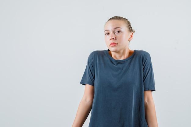 Молодая женщина беспомощно пожимает плечами в серой футболке и выглядит смущенной