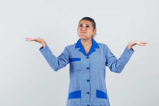 젊은 여자 어깨를 shrugging, 파란색 깅엄 파자마 셔츠에 뺨을 부풀리고 잠겨있는 찾고. 전면보기.