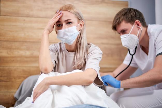 Молодая женщина, больная вирусной инфекцией гриппа в домашнем карантине изоляции, лежит на кровати, пока врач слушает дыхание с помощью стетоскопа. сосредоточиться на белокурой пациентке