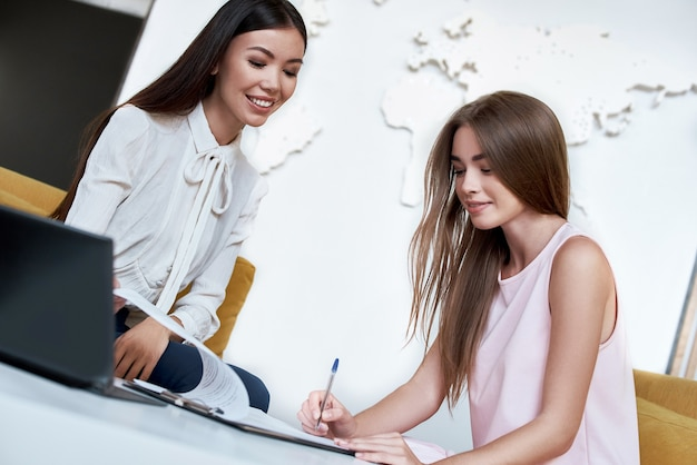 エージェントとの旅行のための契約に署名する若い女性