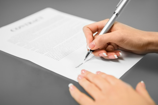 若い女性が雇用契約に署名します。考えて決める。最後のステップ。成功への道。