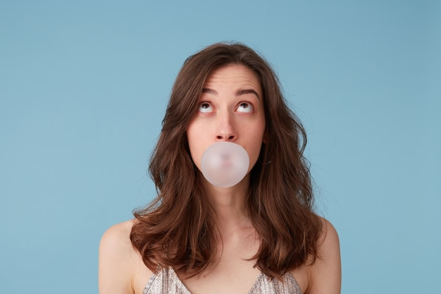 Young woman in silver blouse with bubblegum