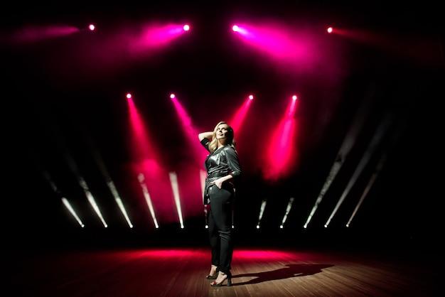 Певица молодая женщина с красочными огнями на концерте