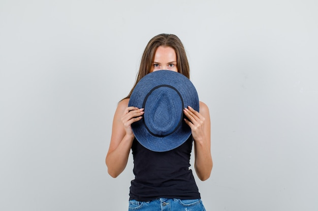 Young woman in singlet, shorts hiding face behind hat