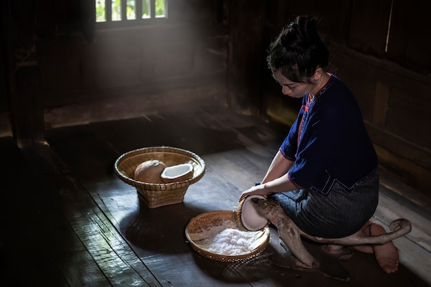 Young woman sit on coconut grater and grate coconut into bowl.