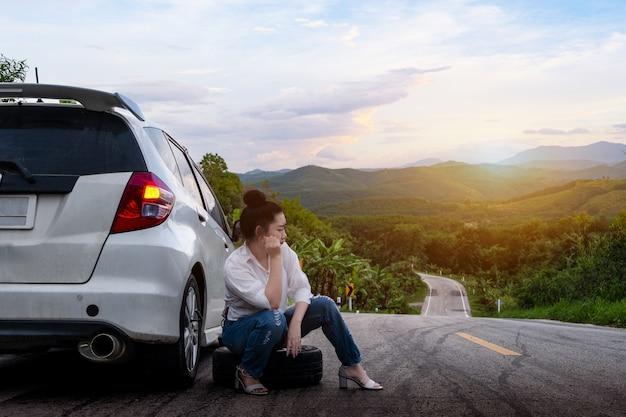 若い女性が公道で助けを求めるために車の近くに座っている