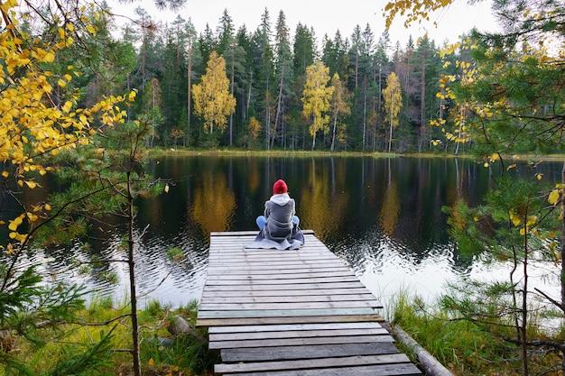 若い女性は、色付きの黄色い金色の木々と秋の森の湖の風景を楽しんでドックに座っています