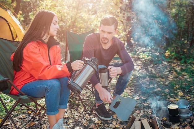 若い女性は折りたたみ椅子に座って、魔法瓶から男のカップにお湯を注ぎます。彼女はそれを正確に行います。男はサーモカップを手に持っています。彼らは一緒に火の中に座っています。