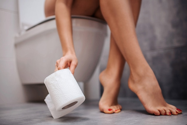 Young woman sit on toilet and get paper from floor