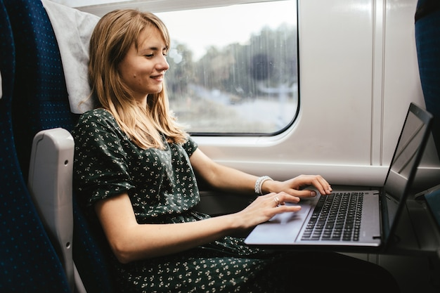 Young woman sit in train alone. work and travel at same time. vacation time or holidays period. typing on laptop keyboard. remote work.