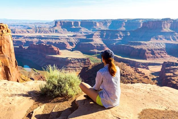 谷のロッキー山脈の頂上に座っている若い女性