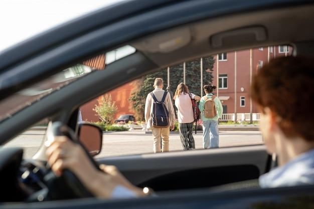 Молодая женщина сидит в машине и смотрит на группу школьников