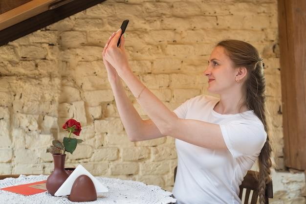 Молодая женщина сидит за столом и делает селфи. фото на телефоне. мобильная фотография.
