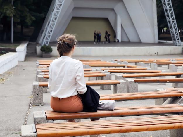 若い女性がリハーサルを行うコンサートシーンの前のベンチに腰を下ろす