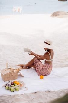 Una giovane donna si siede sul tappeto da spiaggia con un cappello di paglia e vestiti di maglia bianca