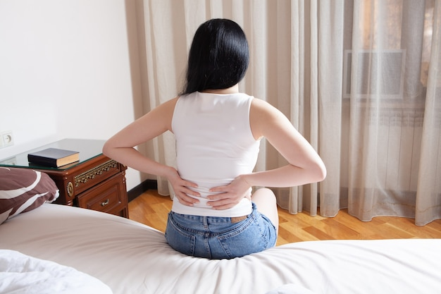 Young woman sits on the bed and holds the kidneys. back pain and kidney pain
