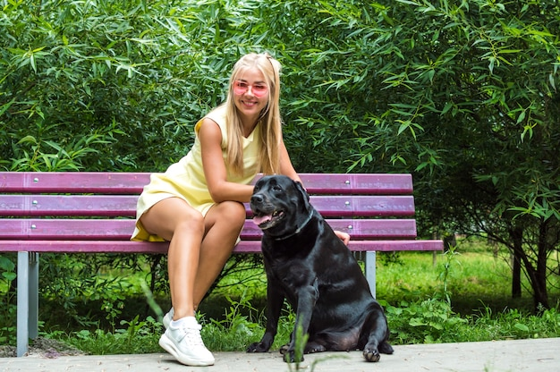 Young woman sits on a bench in a summer park with her big black dog