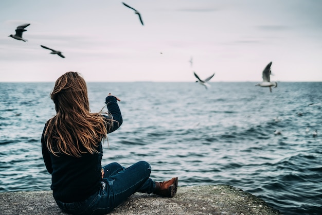 A young woman sits in a blue knitted sweater and jeans by the sea and feeds the seagulls.