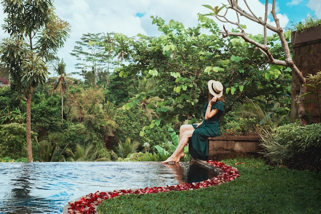 A young woman sits by the open personal pool overlooking the tropical jungle, ubud