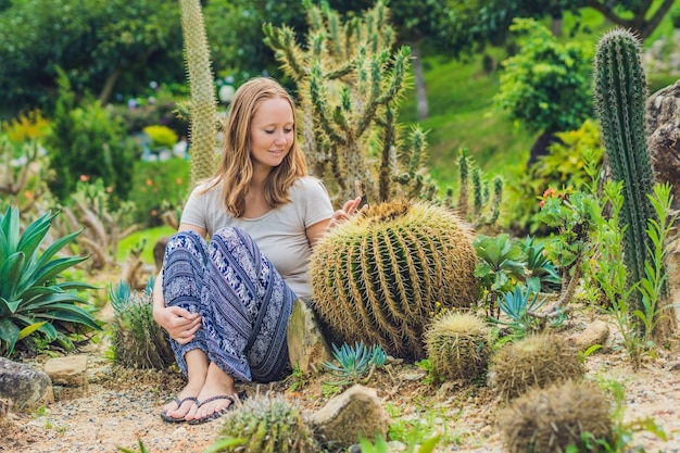 Young woman sits on the ground among the cactus