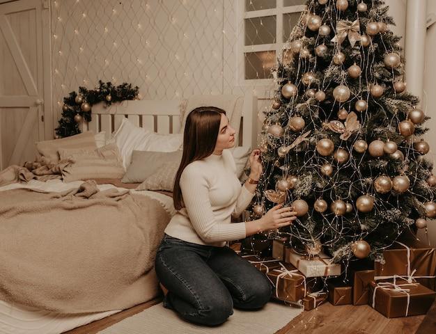 Молодая женщина сидит в белой рубашке для гольфа возле елки в спальне.