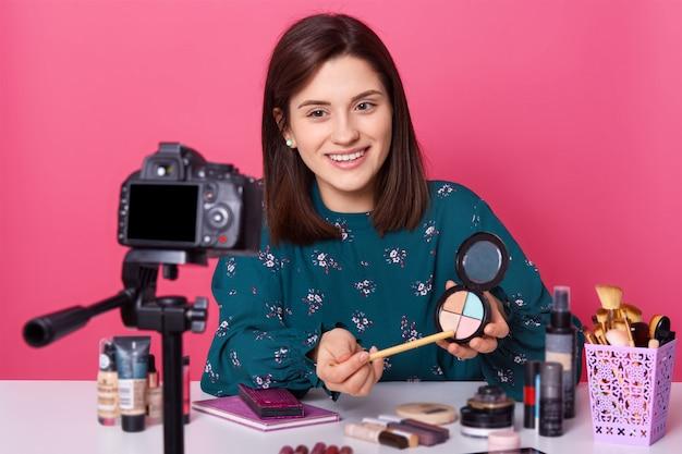 Молодая женщина сидит перед камерой, имеет приятное выражение, в окружении косметики