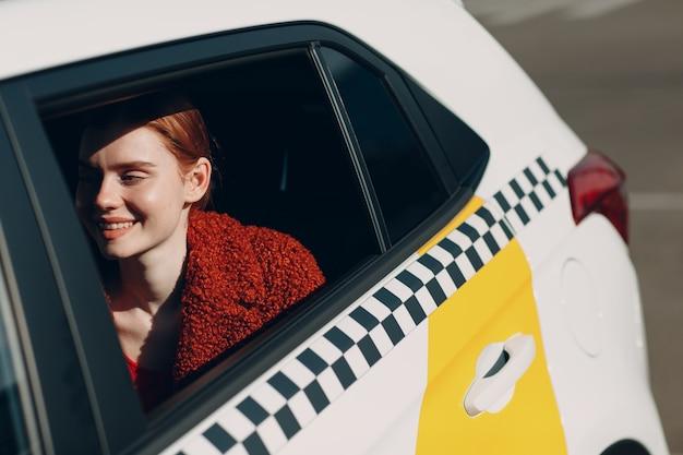 젊은 여자는 뒷좌석에 택시 차에 앉아있다.