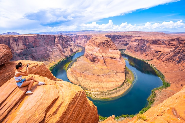 A young woman sits looking at horseshoe bend and the colorado river in the background, arizona. u.s