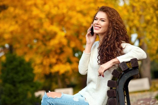 Молодая женщина сидит на скамейке осенью в парке и разговаривает по мобильному телефону