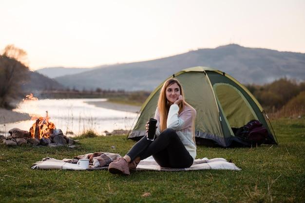 緑のテントとたき火の近くの芝生の上の毛布に若い女性が座る