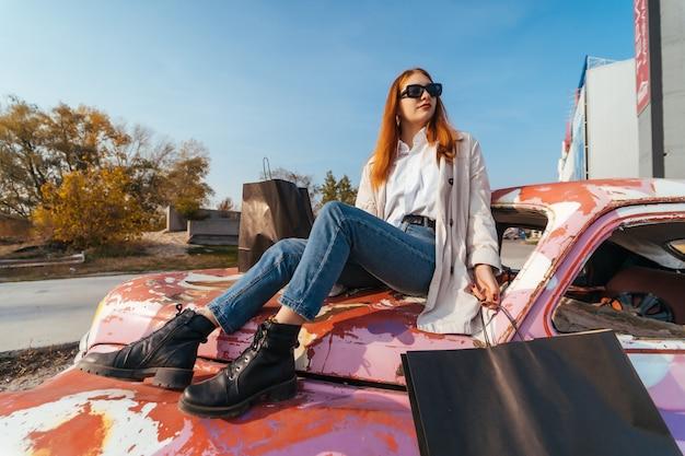 若い女性は古い装飾された車に座っています