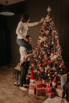 Молодая женщина сидит на спине мужчины и украшает елку