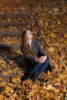 Молодая женщина сидит на опавших листьях в осеннем парке. вертикальная рамка.