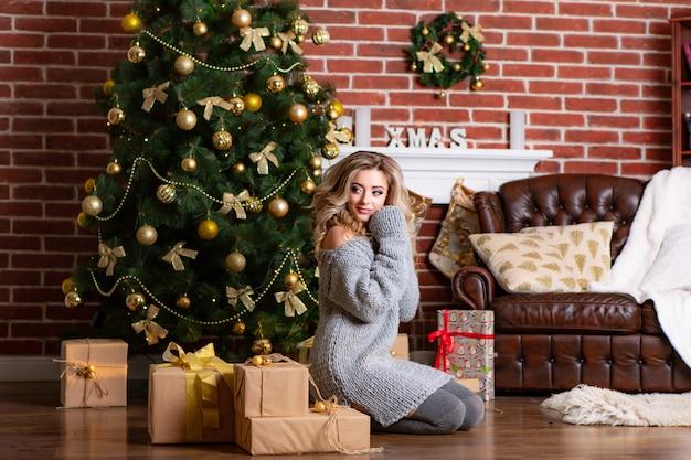 若い女性はおもちゃで飾られたクリスマスツリーの近くの暖かい灰色のドレスで床に座っています。