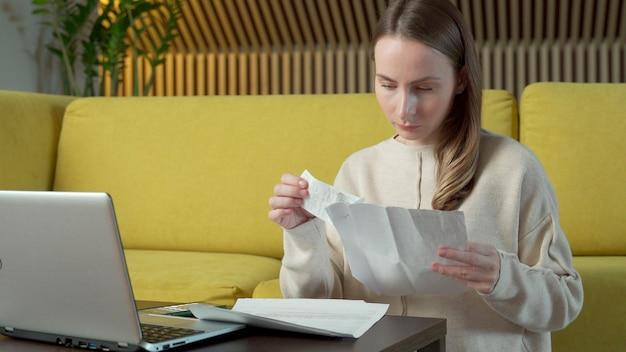 Молодая женщина сидит на полу рядом с желтым диваном за столом с бумажными счетами, чувствуя стресс из-за платежей по банковскому кредиту