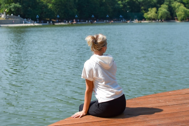 Young woman sits relaxed in nature. outdoor recreation. the girl looks into distance thoughtfully.