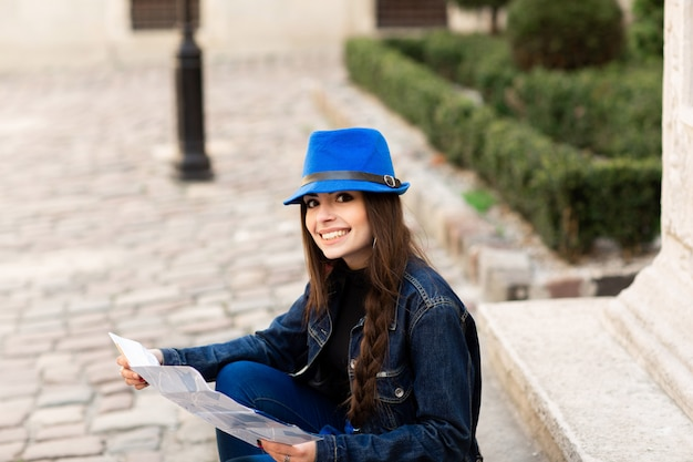 A young woman sits on the stairs in the old courtyard, and reads the map. lviv, ukraine