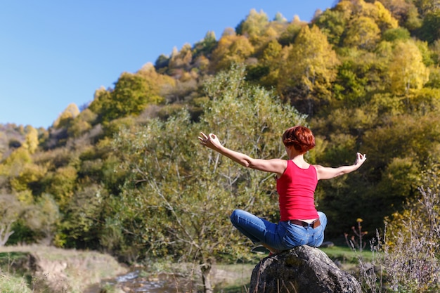 Young woman sits on a stone and meditates against the background of a river, forest and blue sky on a sunny autumn day