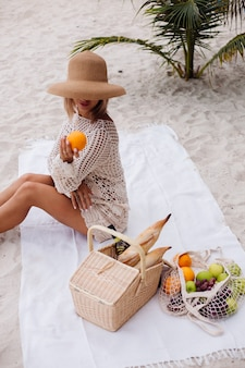 A young woman sits on the towel in a straw hat and a white knitted clothes with picnic basket