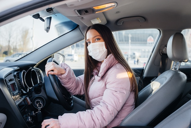 A young woman sits behind the wheel in the car in the mask during the global pandemic and coronavirus. quarantine.