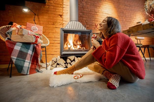 Молодая женщина сидит с рождественскими конфетами у камина. домашний уют и тепло во время зимних праздников