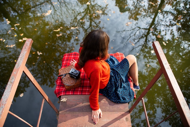 Young woman sits with her back on a bridge near a lake on a sunny day. plaid, camera, suitcase.
