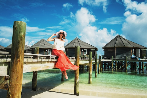 A young woman sits on a wooden bridge near the guest houses while relaxing