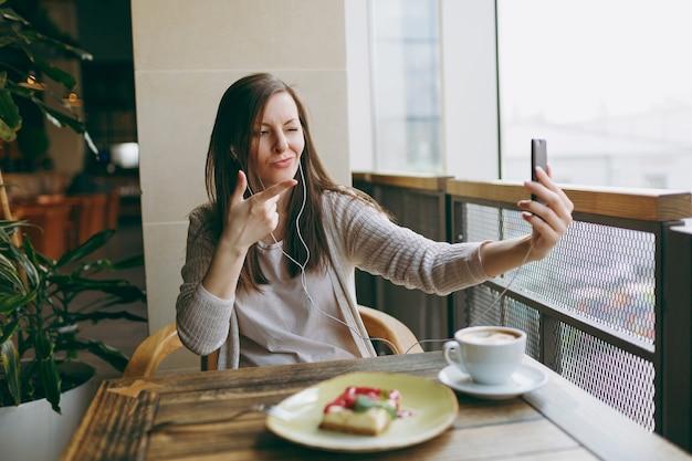カプチーノ、ケーキ、自由時間のレストランでリラックスしてテーブルのコーヒーショップに一人で座っている若い女性。携帯電話で自分撮りをしている若い女性、カフェで休む。ライフスタイルのコンセプト。