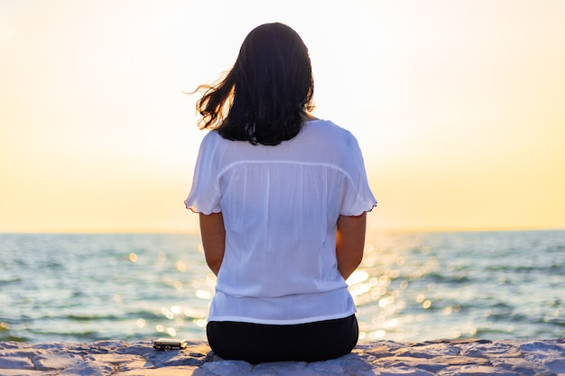 Young woman sitting alone watching the sunset over the ocean